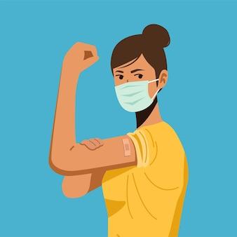 Молодая женщина в защитной маске показывает руку с повязкой после вакцинации от covid-19.