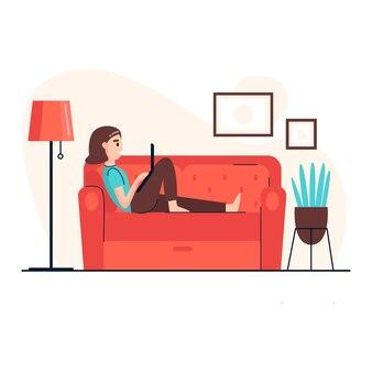 若い女性がラップトップで作業し、自宅のソファに横になっています。在宅勤務。ホームオフィス。