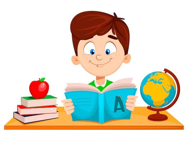 Милый мальчик сидит за столом и читает книгу abc