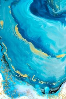 ゴールドラメの背景を持つ抽象的な青い水彩画