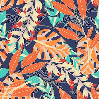 Abstract bright seamless pattern with colorful tropical leaves and plants on dark blue background