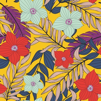 Abstract bright seamless pattern with colorful tropical leaves and plants on yellow
