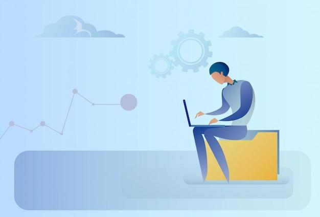 Абстрактный деловой человек, сидя на папке данных, работает портативный компьютер