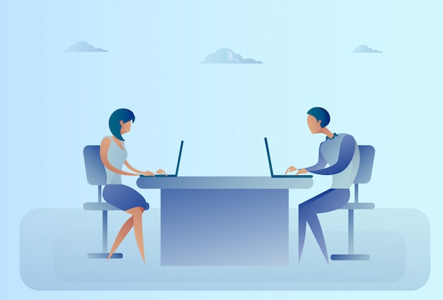 Abstract business man and woman sitting at office desk working laptop computer