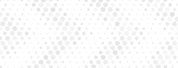 灰色の異なるサイズのドットで作られた抽象的なハーフトーンの背景