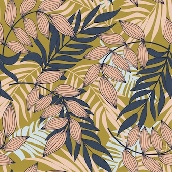 Abstract seamless pattern with colorful tropical leaves and plants on mustard background