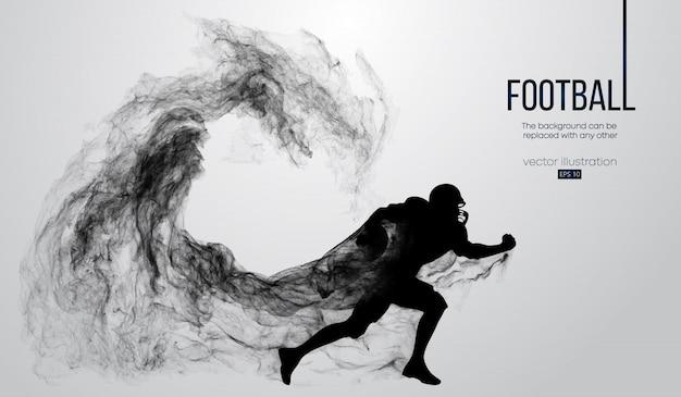 粒子、ほこり、煙、蒸気から白い背景の上のアメリカンフットボール選手の抽象的なシルエット。ボールを持って走るフットボール選手。ラグビー。