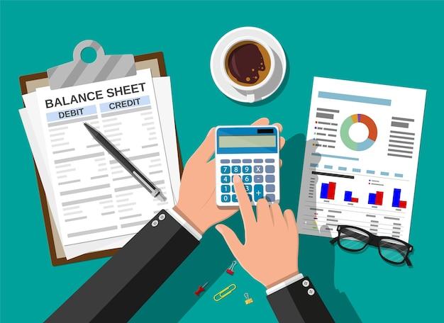 レポートと計算機を持つ会計士は、お金のバランスをチェックします。