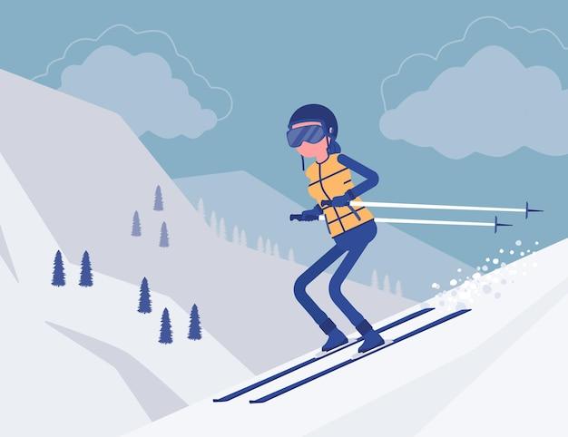 下り坂でスキーをするアクティブなスポーティな女性
