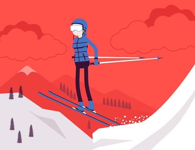 Активная спортивная женщина катается на лыжах, прыгает, наслаждаясь зимними развлечениями на свежем воздухе на курорте с красивой снежной природой, видом на горы, профессиональным зимним туризмом, отдыхом