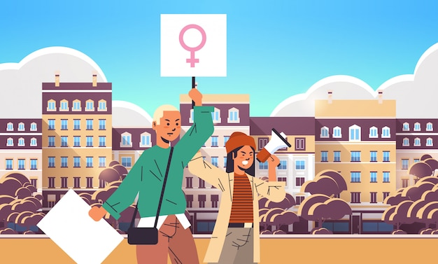 Activists couple holding placards with female gender sign using loudspeaker feminist demonstration girl power movement rights protection women empowerment concept portrait cityscape horizontal