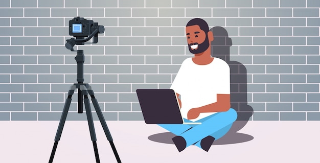 African american blogger using laptop recording video blog with digital camera on tripod live streaming social media blogging concept brick wall background full length horizontal
