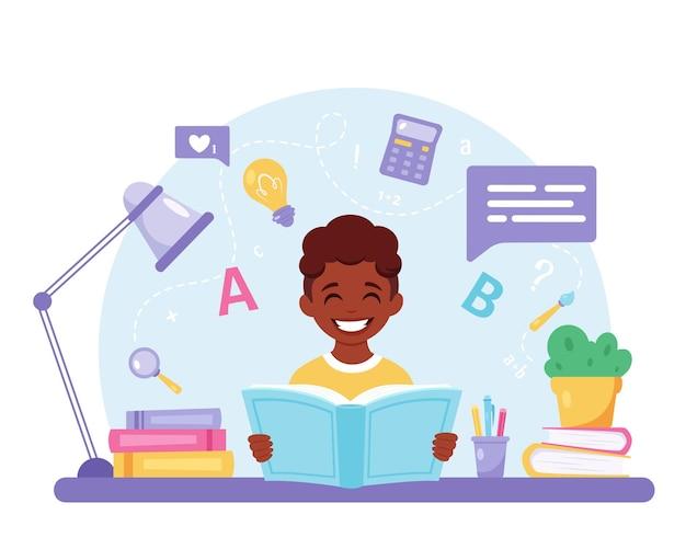 学校に戻って宿題をしている本の少年を読んでアフリカ系アメリカ人の少年