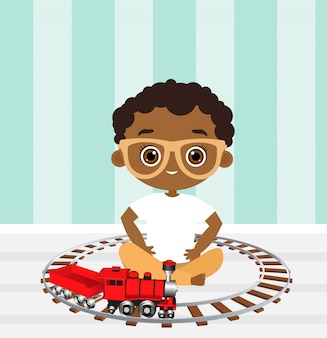 African american boy with glasses and toy train. boy playing with train