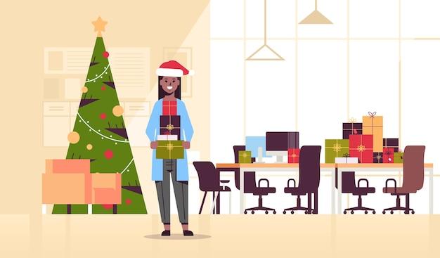 アフリカ系アメリカ人ビジネスウーマンギフトプレゼントボックスメリークリスマス新年あけましておめでとうございます冬の休日お祝いコンセプトモダンオフィスインテリアフラットイラスト