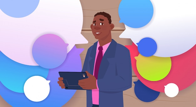 African american businessman holding tablet speak over colorful chat bubbles