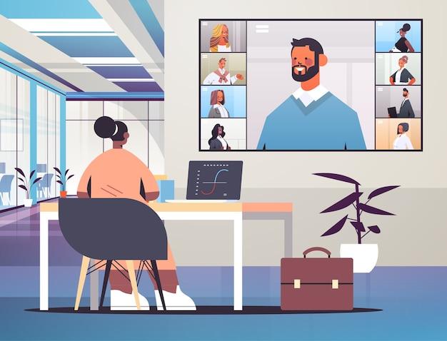 グループビデオ通話オフィスのインテリアイラストで働く企業のオンライン会議ミックスレースチームの間にビジネスマンと話し合うアフリカ系アメリカ人の実業家