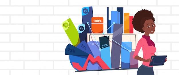 プレゼンテーションを保持しているアフリカ系アメリカ人の実業家抽象的なチャートとグラフの上に立つビジネスの女性