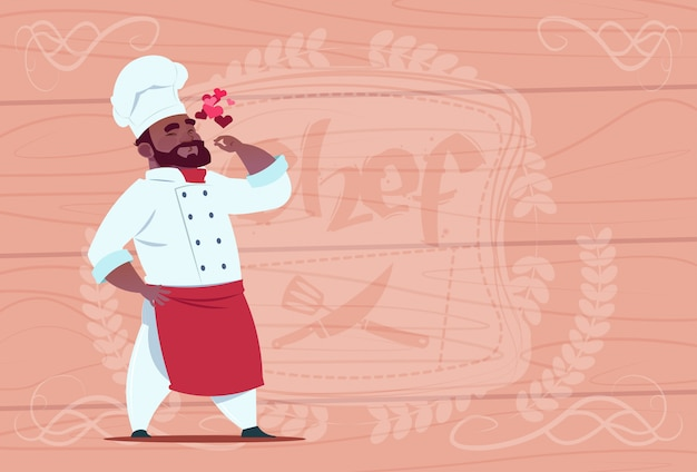 African american chef cook happy smiling cartoon restaurant chief in white uniform over wooden textured background