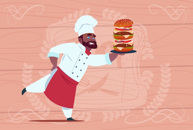 African american chef cook hold big burger smiling cartoon restaurant chief in white uniform over wooden textured background