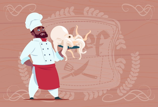 African american chef cook hold octopus smiling cartoon restaurant chief in white uniform over wooden textured background