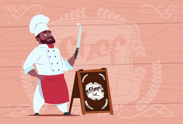 African american chef cook holding knife smiling cartoon character in white restaurant uniform over wooden textured background