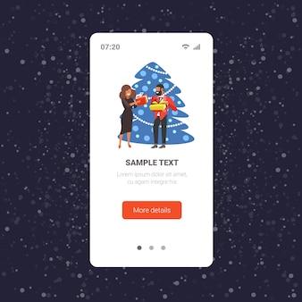 アフリカ系アメリカ人のカップルがお互いにギフトプレゼントボックスを与えるメリークリスマス冬休みのお祝いのコンセプトスマートフォン画面オンラインモバイルアプリ全長ベクトルイラスト