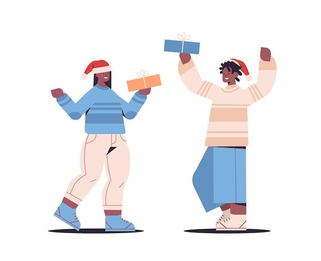 산타 클로스 모자에 아프리카 계 미국인 부부는 포장 된 선물 상자 새 해 복 많이 받으세요 그리고 메리 크리스마스 휴일 축 하 개념 가로 전체 길이 벡터 일러스트 레이 션을 들고