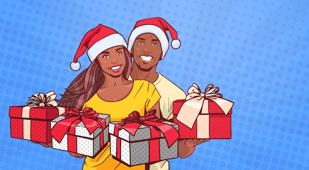 African american couple wearing santa hats hold presents happy man and woman over comic pop art back