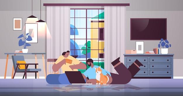 노트북 온라인 쇼핑 개념을 사용하여 신용 카드를 가진 아프리카계 미국인 커플 현대 거실 내부 수평 전체 길이로 물건을 주문하는 남자 여자