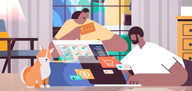 노트북 온라인 쇼핑 개념을 사용하여 신용 카드를 사용하는 아프리카계 미국인 커플 현대 거실 내부 수평으로 물건을 함께 주문하는 남자 여자