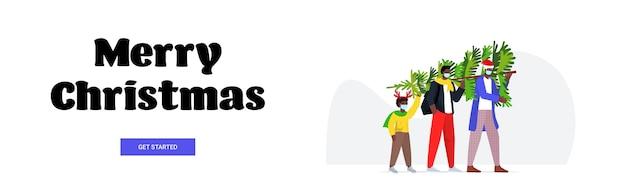 コロナウイルスパンデミック年末年始のお祝いのコンセプト水平バナーを防ぐためにマスクを身に着けている子供とクリスマスツリーの親を運ぶアフリカ系アメリカ人の家族