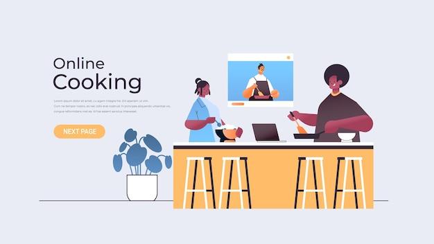アフリカ系アメリカ人の食品ブロガーのカップルがウェブブラウザウィンドウで男性シェフとのビデオチュートリアルを見ながら料理を準備するオンライン料理のコンセプト水平コピースペースの図