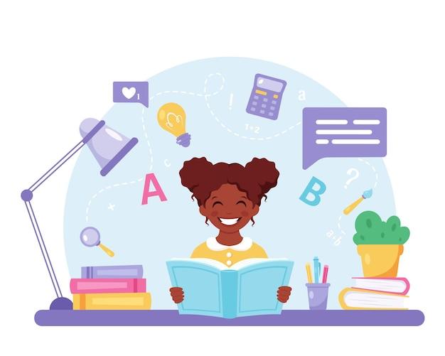 学校に戻って宿題をしている本の女の子を読んでアフリカ系アメリカ人の女の子