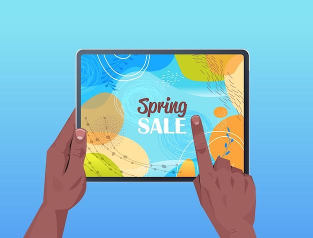 画面の水平方向の図に春のセールバナーチラシまたはグリーティングカードとタブレットpcを使用してアフリカ系アメリカ人の人間の手