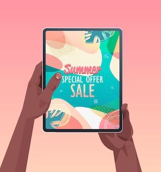 画面上の夏のセールバナーチラシまたはグリーティングカードとタブレットpcを使用してアフリカ系アメリカ人の人間の手