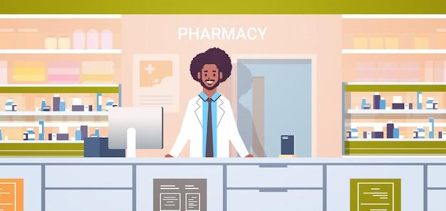 アフリカ系アメリカ人男性医師薬剤師が薬局のカウンターに立っている現代のドラッグストアインテリア医学ヘルスケア概念水平肖像