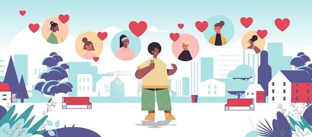 アフリカ系アメリカ人の男性がオンラインデートアプリで混血の女性とチャット仮想会議社会的関係コミュニケーション愛の概念を見つける都市公園都市景観水平全長レトラティ