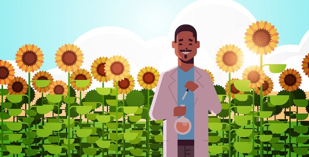 African american man scientist holding test tube making experiment on sunflowers field research science agriculture farming concept flat horizontal portrait