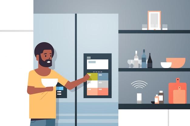 African american man touching refrigerator screen