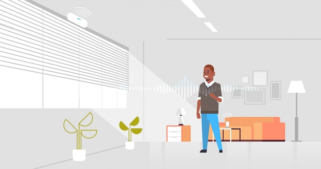 African american man using smart speaker voice recognition
