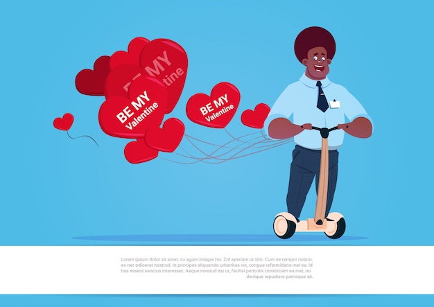 African american man with heart shaped air balloons riding electric scooter happy valentine day concept