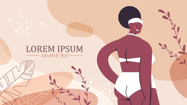 アフリカ系アメリカ人のプラスサイズの女の子のビキニの太りすぎの女性の立っているポーズはあなたの体の概念の肖像画を愛している