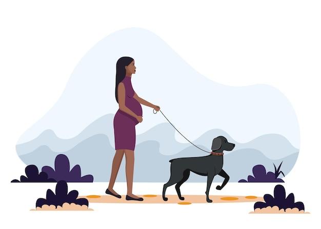Афро-американская беременная женщина гуляет с собакой.