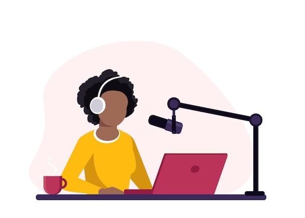 Афро-американский радиоведущий сидит перед микрофоном. молодая женщина в наушниках работает в радиостудии