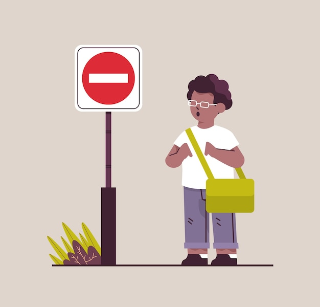 African american schoolboy with backpack standing near red stop road sign road safety