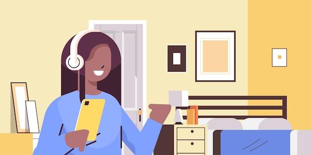 스마트 폰을 사용하고 헤드폰에서 음악을 듣고 아프리카 계 미국인 여학생 집 초상화에서 편안한 가제트와 웃는 소녀