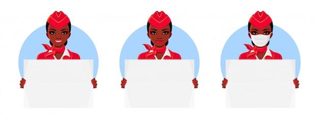 빨간색 유니폼을 입고 아프리카 계 미국인 스튜어디스. 빈 현수막을 들고 스튜어디스. 미소와 의료 마스크 여자입니다.