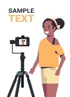 African american woman blogger recording video blog with digital camera on tripod live streaming social media blogging concept portrait vertical copy space