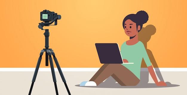 Афро-американский блоггер, использующий ноутбук, записывающий видеоблог с цифровой камерой на штативе, в прямом эфире, социальные медиа, блоги, полная длина, горизонтальный